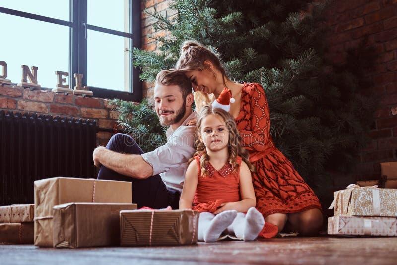 Família atrativa que senta-se em um assoalho cercado por presentes ao lado da árvore de Natal em casa imagem de stock