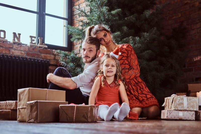 Família atrativa que senta-se em um assoalho cercado por presentes ao lado da árvore de Natal em casa imagens de stock royalty free