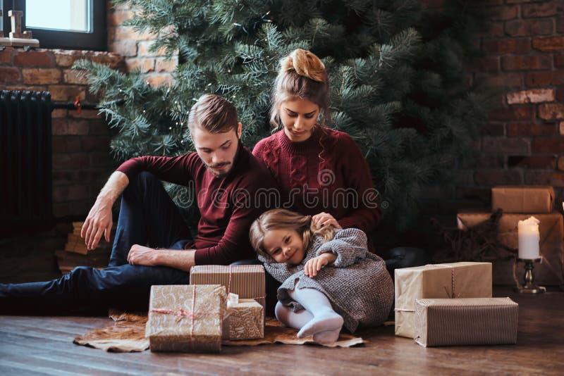Família atrativa que senta-se junto em um assoalho cercado por presentes ao lado da árvore de Natal imagens de stock royalty free