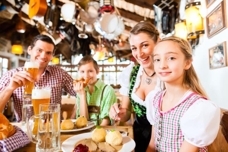 Família bávara em comer alemão do restaurante imagem de stock royalty free