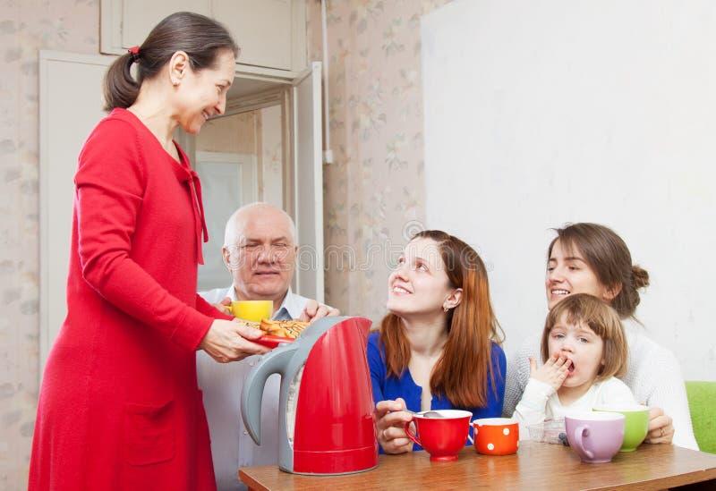 A família bebe o chá e come bolos fotos de stock