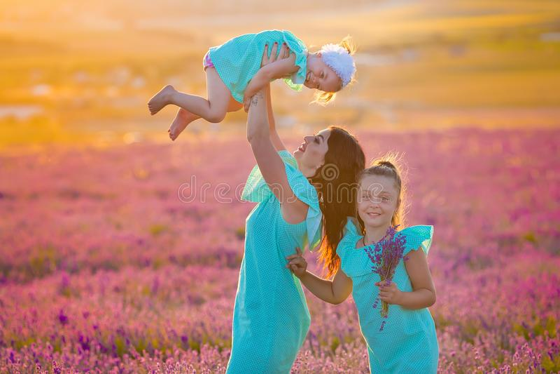 A família bonita de meninas bonitos aprecia a vida com o prado do por do sol do poder da menina sobre da alfazema Mamã e filhas d imagem de stock