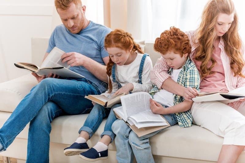 Família bonita do ruivo que senta-se no sofá e nos livros de leitura junto foto de stock royalty free