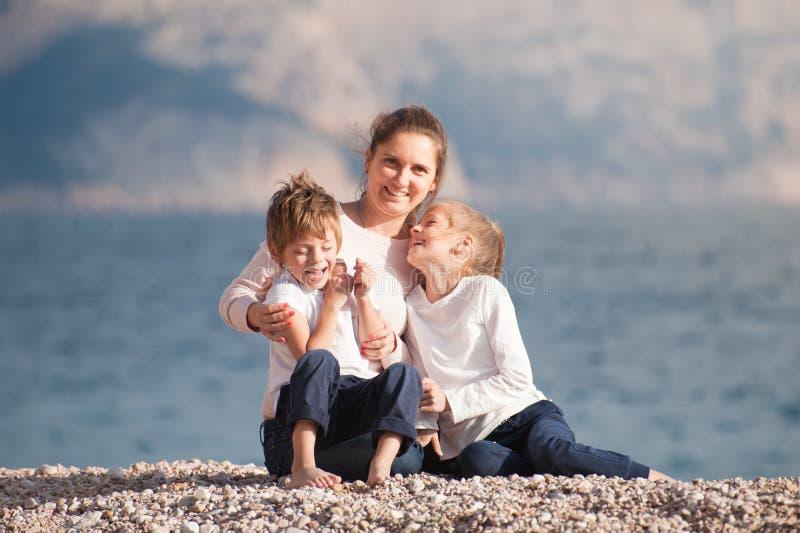 Família bonita feliz que consiste na mãe e filho e filha de sorriso que sentam-se na praia do mar no dia fresco do por do sol do  foto de stock