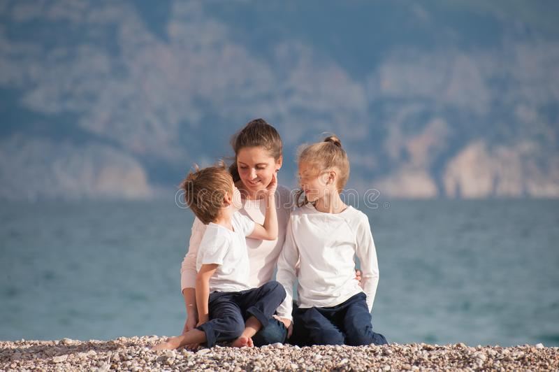 A família bonita feliz que consistem na mãe de sorriso e duas crianças que sentam-se no mar encalham no dia fresco do por do sol  fotografia de stock