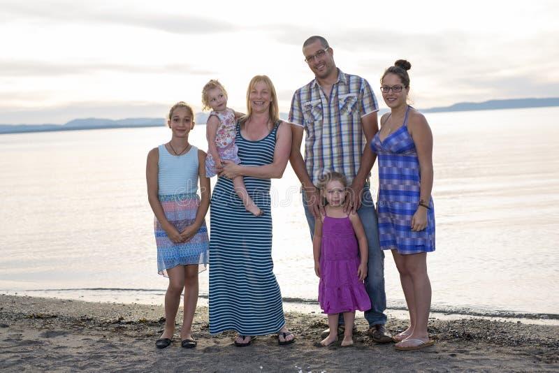 Família bonita feliz que está no por do sol da praia fotografia de stock
