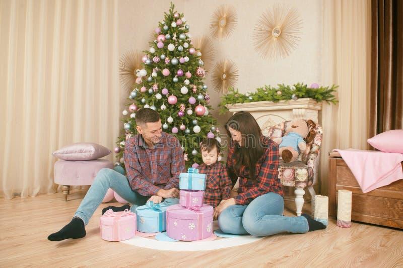 Família bonita feliz que senta-se no assoalho com presentes do Natal e fotos de stock