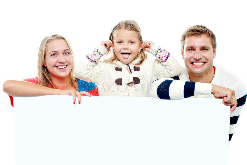 Família bonita nova atrás da placa em branco branca do anúncio fotos de stock royalty free