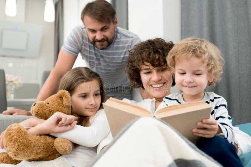 Família bonita que lê alto imagens de stock