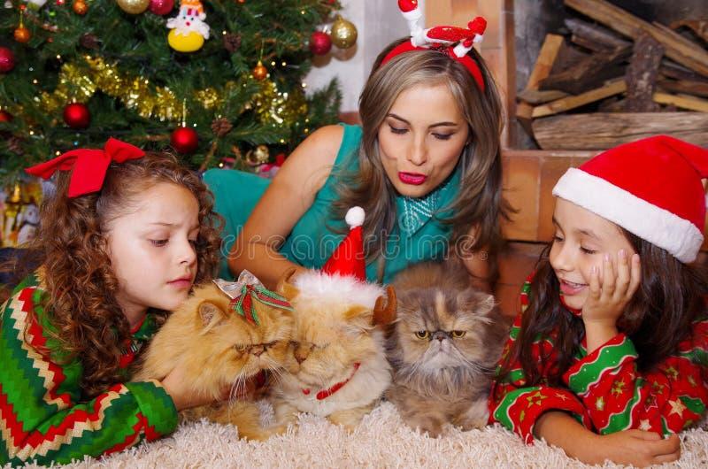 A família bonita que veste um Natal vest-se-ir, abraçando seus gatos, a menina encaracolado com um laço vermelho em seu cabelo qu foto de stock royalty free