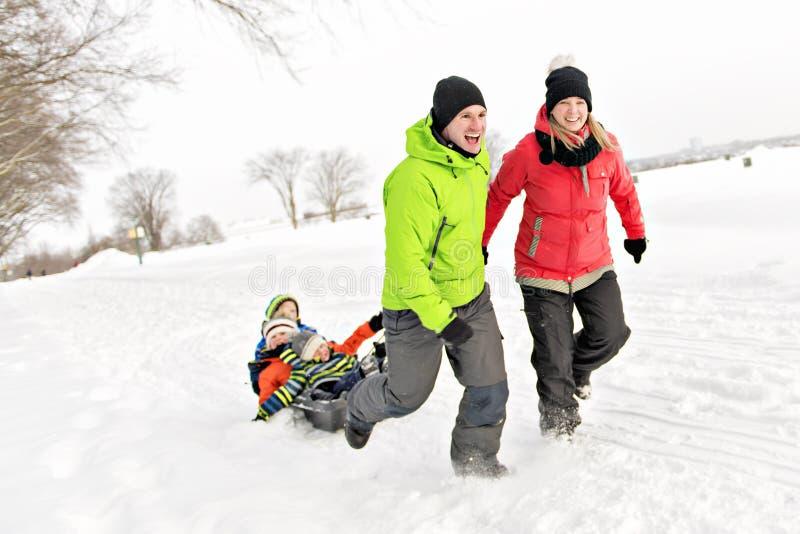 Família bonito que puxa o pequeno trenó com a paisagem nevado fotos de stock