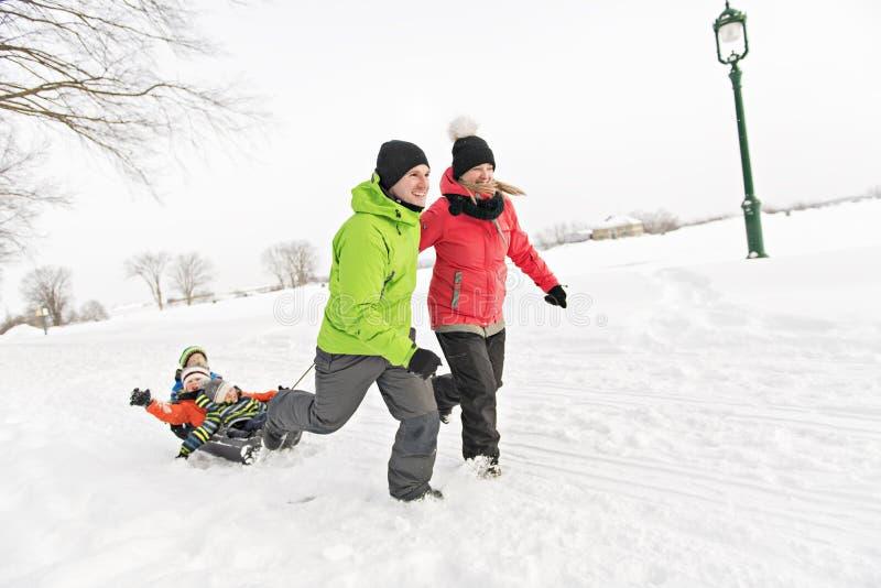 Família bonito que puxa o pequeno trenó com a paisagem nevado fotografia de stock royalty free