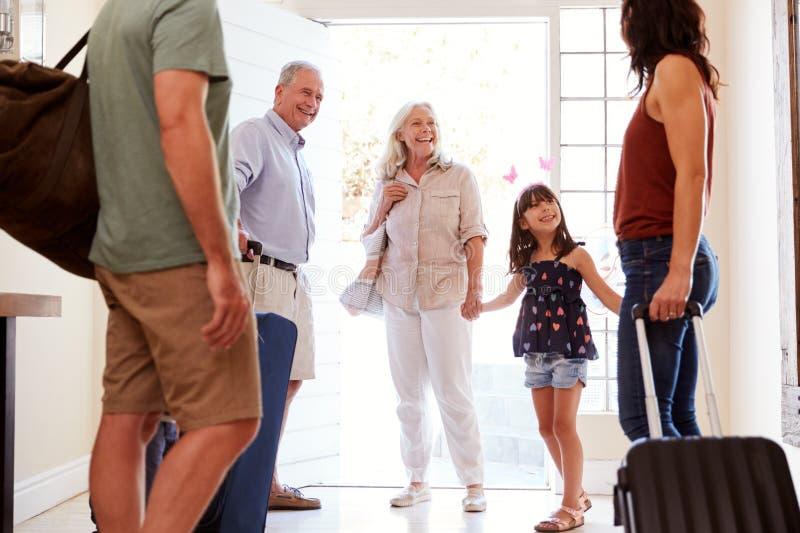 Família branca de três gerações na porta da rua que prepara-se para sair em casa para ir acima no feriado, fim, colheita foto de stock royalty free
