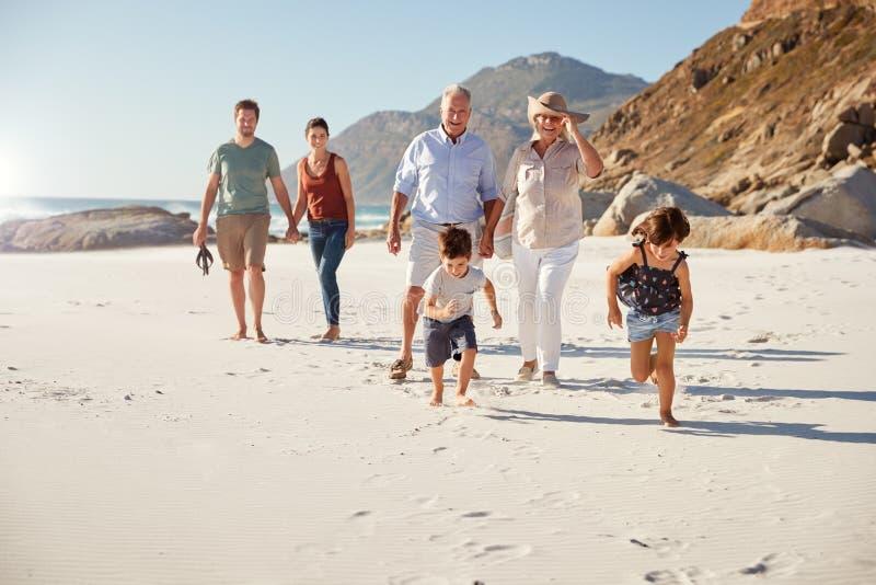 Família branca de três gerações que anda junto em uma praia ensolarada, crianças que correm adiante imagem de stock