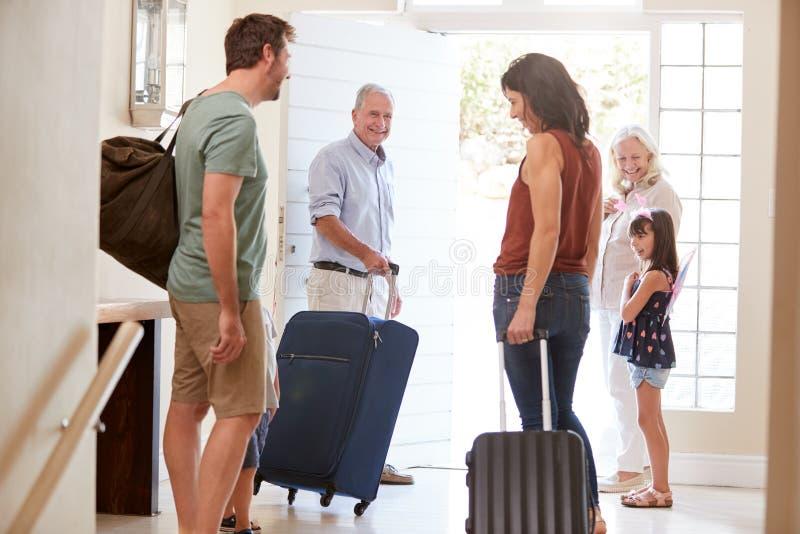 Família branca de três gerações que prepara-se para sair em casa para ir acima no feriado, comprimento completo, fim fotos de stock royalty free