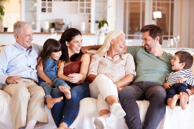 Família branca feliz de três gerações que senta-se em um sofá em casa que olha se, vista dianteira foto de stock
