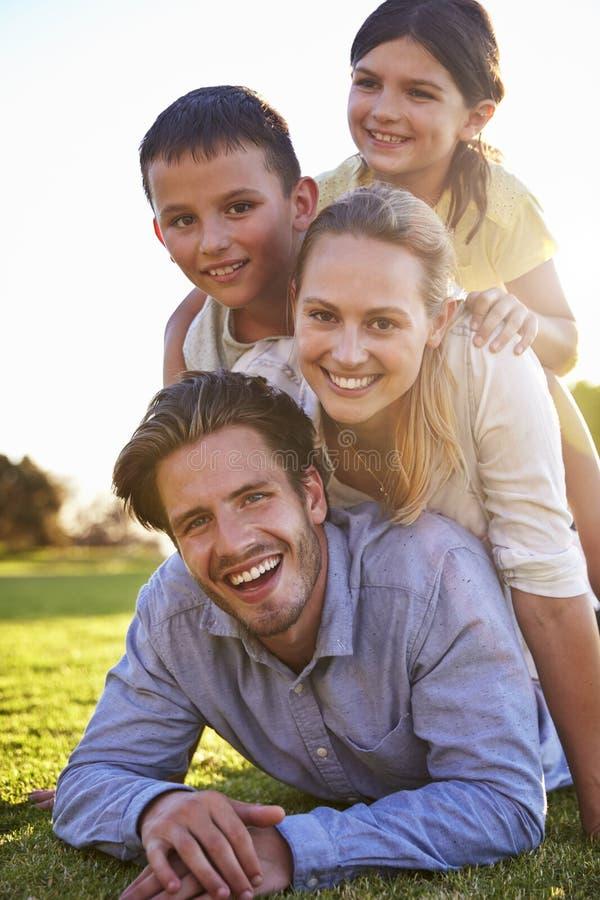 Família branca feliz que encontra-se em uma pilha na grama fora fotografia de stock royalty free