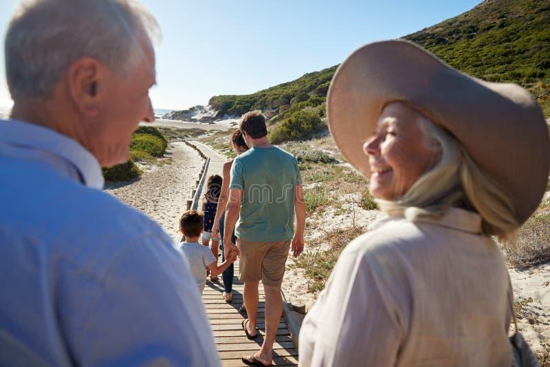 Família branca que anda em uma praia, avós de três gerações no primeiro plano, sobre a opinião do ombro foto de stock royalty free