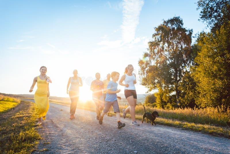 Família brincalhão que corre e que joga em um trajeto na paisagem do verão foto de stock royalty free