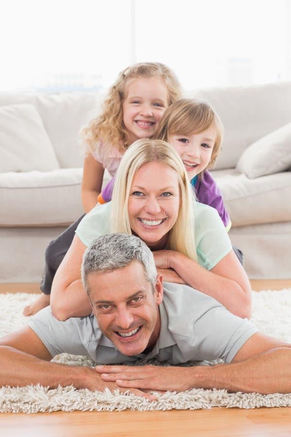 Família brincalhão que encontra-se em se na sala de visitas foto de stock royalty free