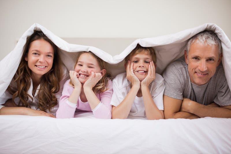 Família brincalhão que encontra-se sob um duvet imagens de stock