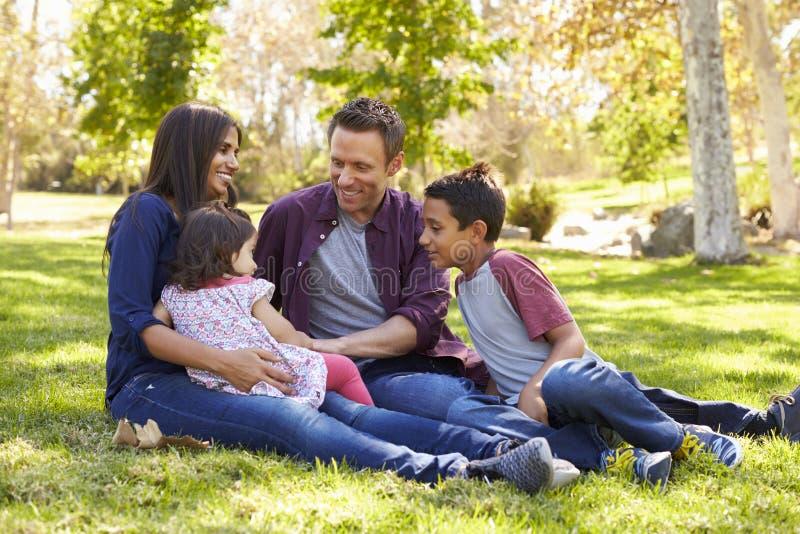 Família caucasiano asiática da raça misturada que senta-se na grama em um parque fotografia de stock