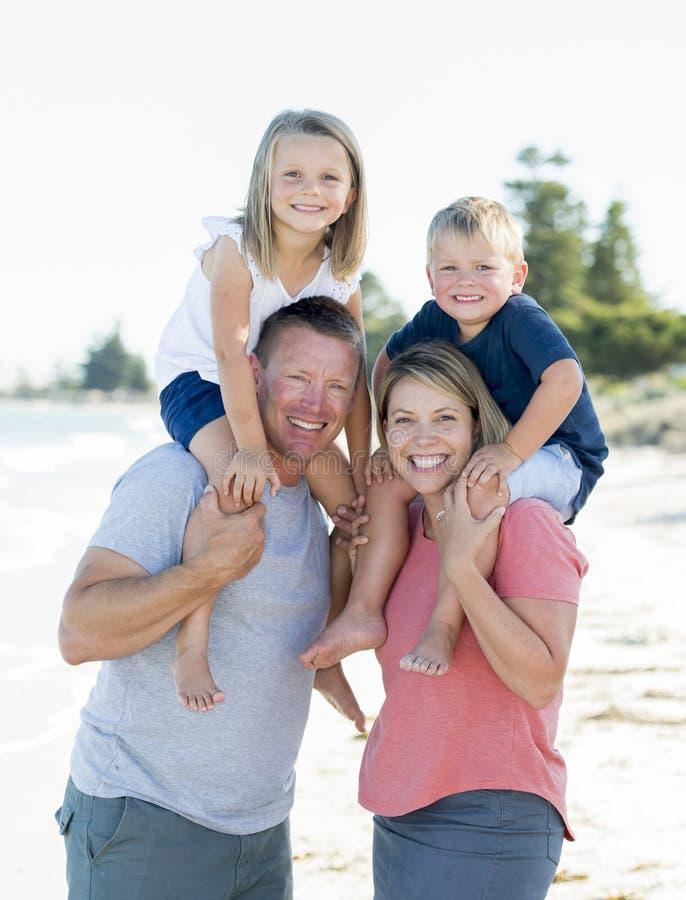 Família caucasiano bonita feliz nova que tem feriados na praia que sorri com a mãe e o pai que levam o filho e os jovens pequenos imagens de stock