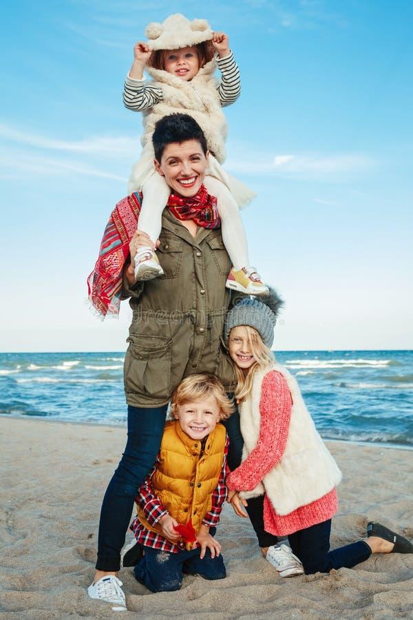 a família caucasiano branca, mãe com três crianças caçoa o aperto do riso de sorriso na praia do mar do oceano no por do sol fora imagens de stock