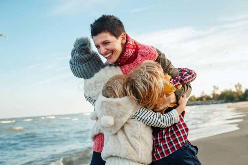a família caucasiano branca, mãe com três crianças caçoa o aperto do riso de sorriso na praia do mar do oceano no por do sol fora imagem de stock royalty free