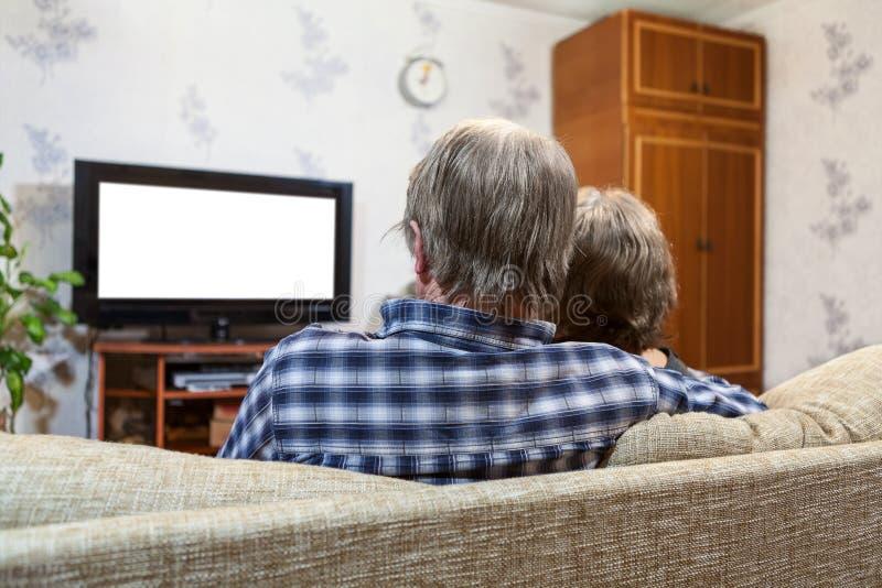 Família caucasiano de três povos que sentam-se no sofá e na tevê de observação, vista traseira, tela branca isolada fotos de stock