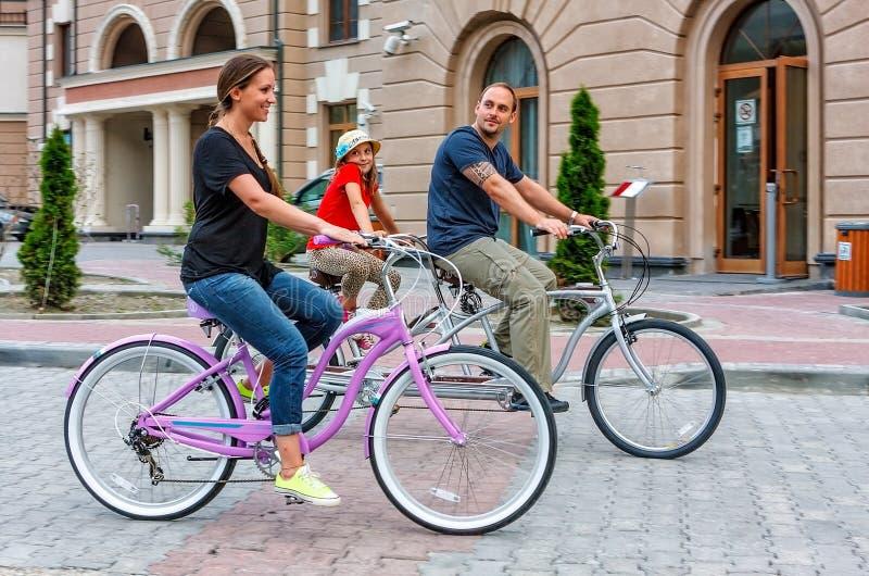 A família caucasiano feliz do pai, a mãe e a filha montam bicicletas fora na rua no verão no fundo das construções do hotel fotos de stock royalty free