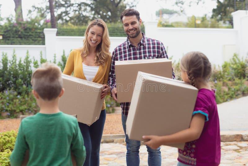 Família caucasiano feliz que guarda caixas de cartão na jarda da casa fotografia de stock