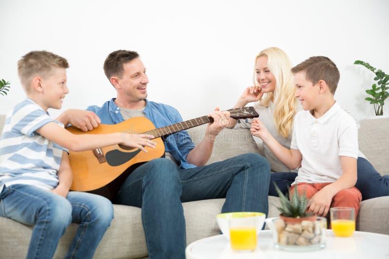 Família caucasiano feliz que sorri, jogando a guitarra e cantando músicas junto na casa moderna confortável foto de stock royalty free