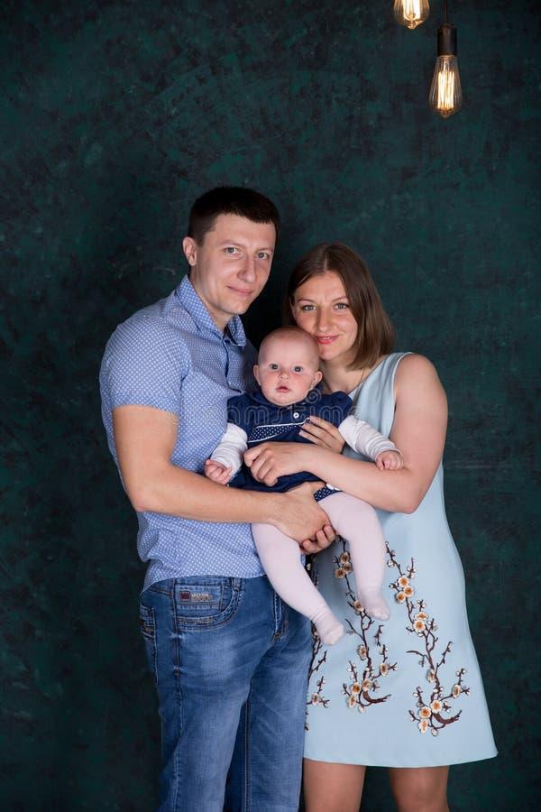 Família caucasiano nova feliz que levanta no estúdio imagem de stock