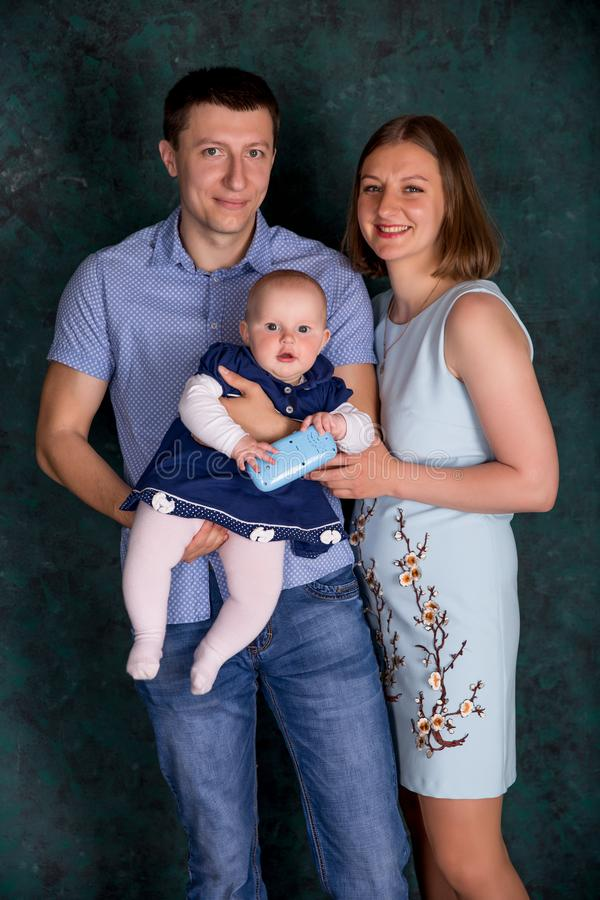 Família caucasiano nova feliz que levanta no estúdio imagens de stock royalty free