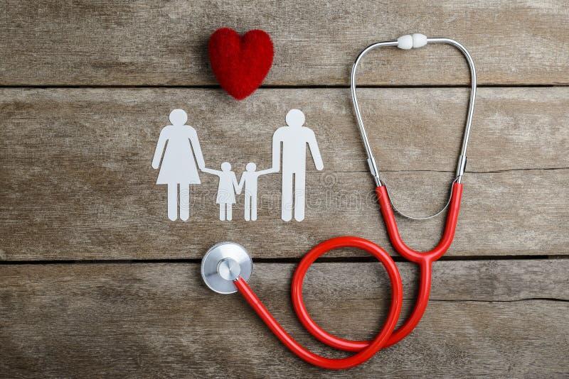 Família chain vermelha do coração, do estetoscópio e do papel na tabela de madeira imagens de stock