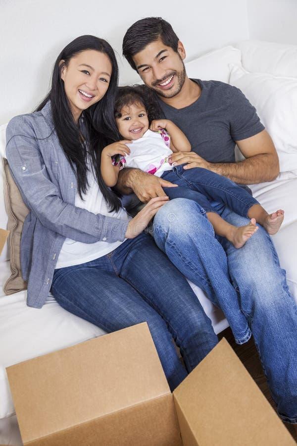 Família chinesa asiática que desembala as caixas que movem a casa imagem de stock royalty free