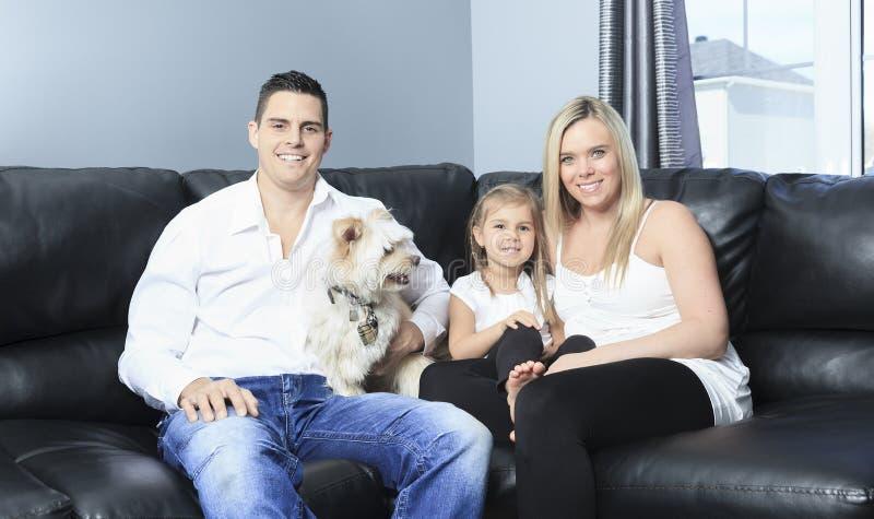 A família com animais de estimação senta-se no sofá em casa foto de stock royalty free