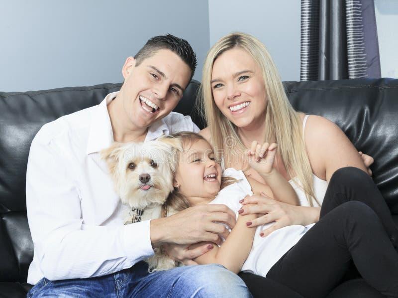 A família com animais de estimação senta-se no sofá em casa imagens de stock royalty free