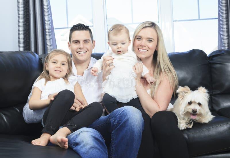 A família com animais de estimação senta-se no sofá em casa fotos de stock