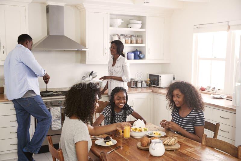 Família com as crianças adolescentes que comem o café da manhã na cozinha foto de stock royalty free