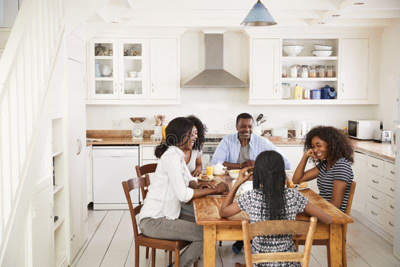 Família com as crianças adolescentes que comem o café da manhã na cozinha foto de stock
