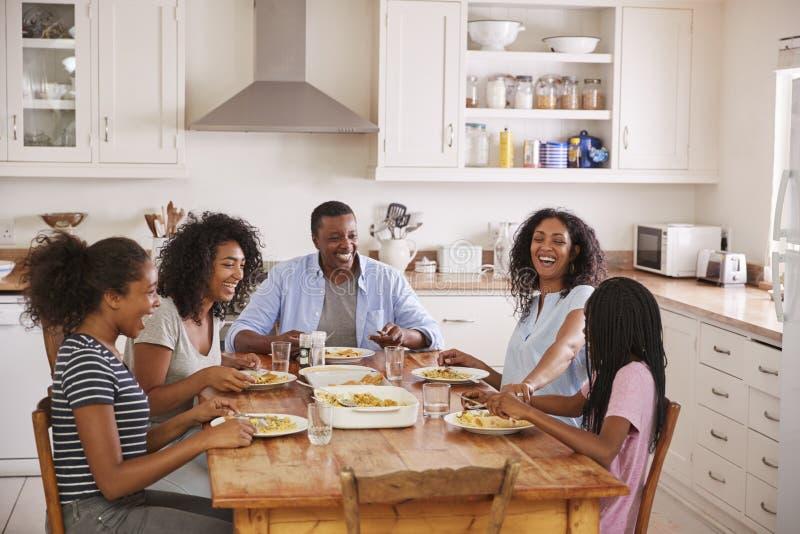 Família com as crianças adolescentes que comem a refeição na cozinha imagens de stock