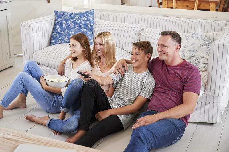 Família com as crianças adolescentes que sentam-se na tevê de Sofa Watching junto imagem de stock royalty free