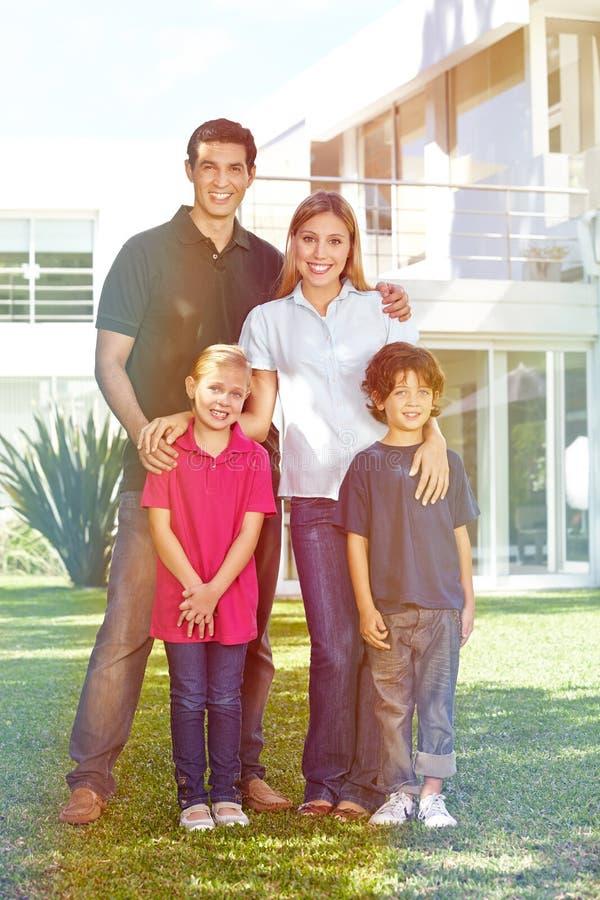 Família com as crianças na frente da casa no jardim fotografia de stock royalty free