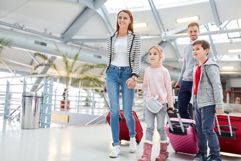 Família com as crianças na maneira ao voo de conexão imagem de stock