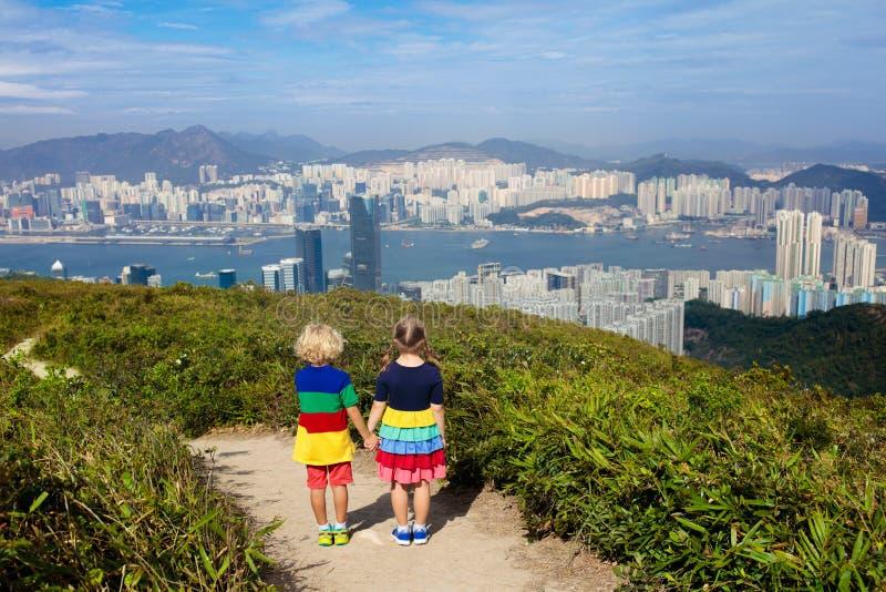 Família com as crianças que caminham em montanhas de Hong Kong Paisagem bonita com os arranha-céus dos montes, do mar e da cidade imagem de stock