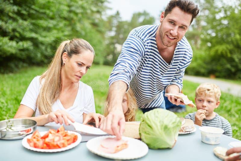 Família com as crianças que comem o alimento no jardim fotografia de stock royalty free