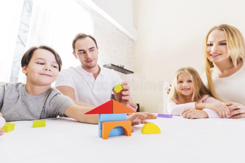 Família com as crianças que constroem a casa foto de stock