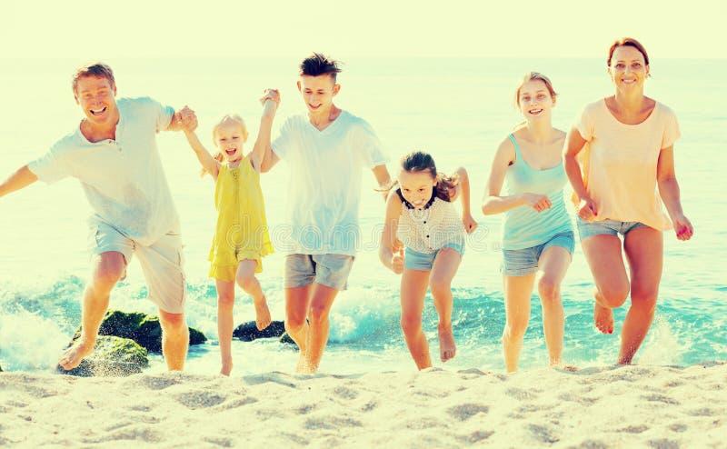 Família com as crianças que correm junto na praia fotografia de stock